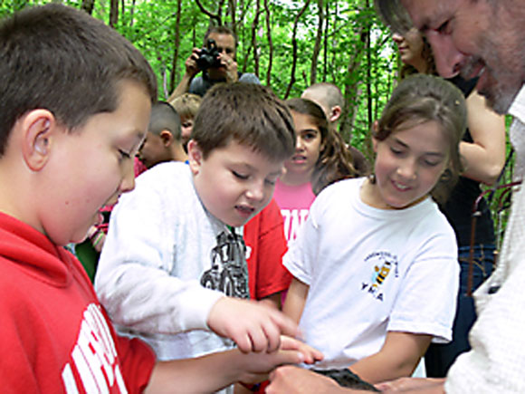 Students gather around to look at an interesting rock from the river with Monroe resident Gary Pannone, right, of Trout Unlimited.