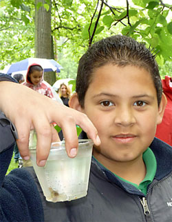 A Trout in the Classroom student displays the fry he has raised before setting it free.