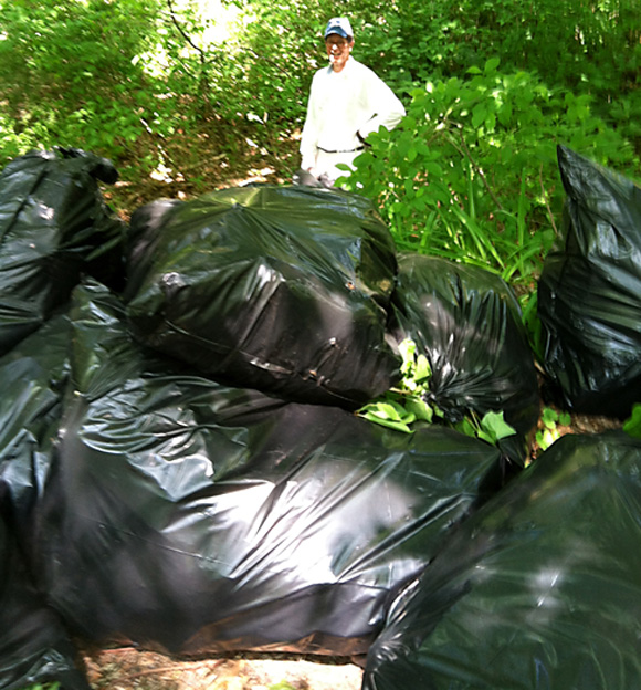 Bob Campbell stacks bags filled with Japanese Knotweed cut and removed from the banks of the Mill River along Congress Street. The nearly 20 bags stacked represent only a few hours work on the project.